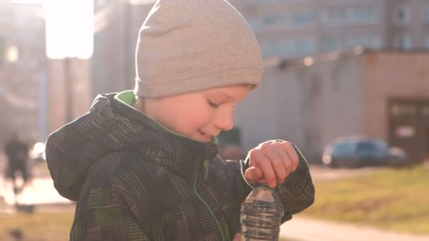 Boy drinks water from the bottle on the street. Opens the bottle, drinks water and closes the bottle.