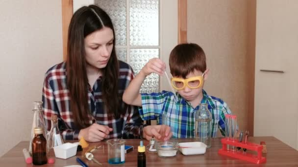 Experiments on chemistry at home. Mother and son do a science experiment together.