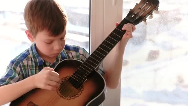 Playing a musical instrument. Boy plays the guitar sitting on the windowsill.