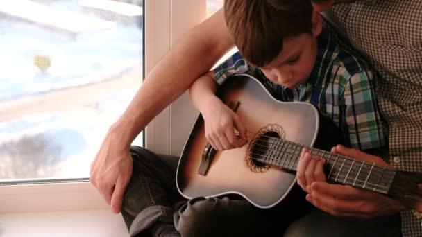 Hra na hudební nástroj. Otec učí svého syna hrát na kytaru, sedí na okenním parapetu.