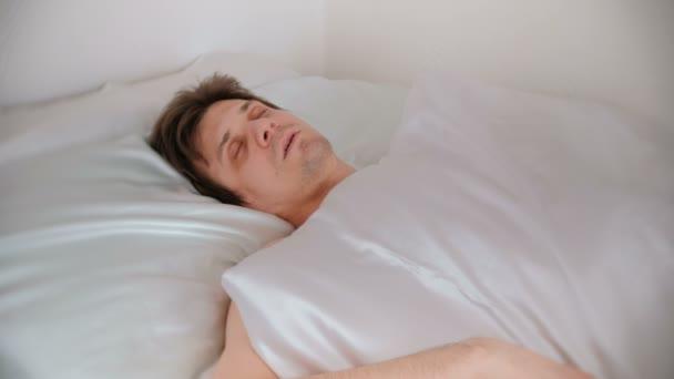 Člověk spí posteli sám zahrnuty deku. Pohled zepředu.