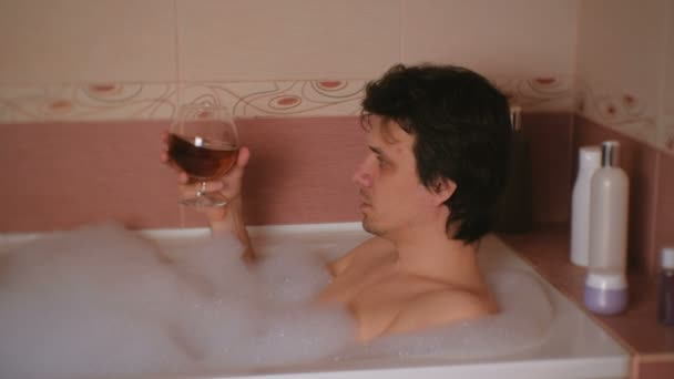 Člověk bere koupel a pije koňak. Deprese a problémy v životě. Boční pohled.