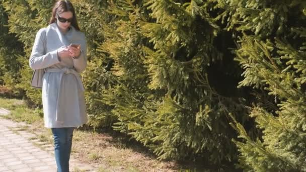 Young brunette woman in sunglasses and coat walks in city park and looks at phone.