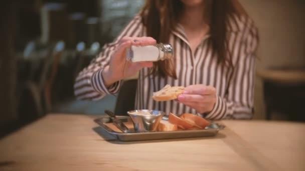 Žena bruneta sůl sendvič s paštikou v kavárně
