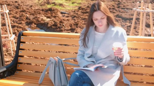 Young beautiful brunette woman student sits on the bench in spring park, reads a book and drinks coffee.