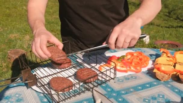 Člověk dělá sendviče. Přebírá kotlety na grilu a umístí na chleba se sýrem a pepřem. Rukou detail