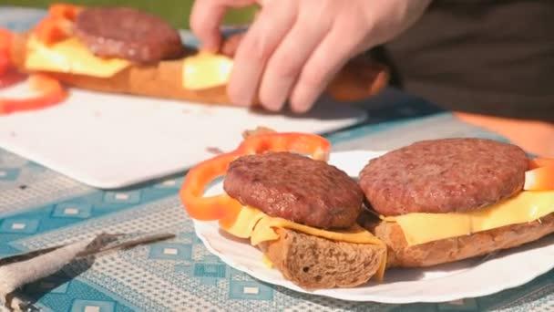 Luomo fa panini con cotolette, formaggio, pane e pepe. Close-up mani