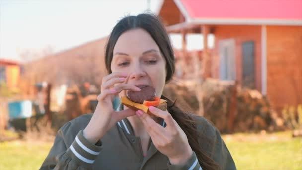 Bruneta Mladá krásná žena jí sendvič na dvorku