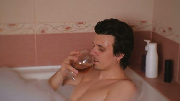 Fiatal férfi vesz egy fürdőt, hab, és iszik a whisky. És mosolyogva néz a kamera.