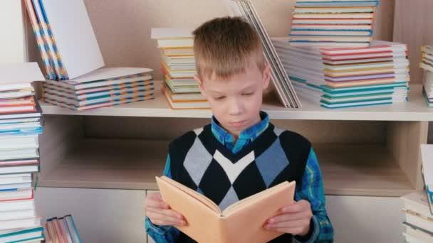 Sedm rok starý chlapec pozorně čte knihu sedí mezi knihami