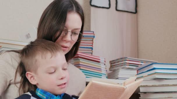 Mutter und Sohn lesen zusammen ein Buch. Mama in Brille. Gesichter aus nächster Nähe.