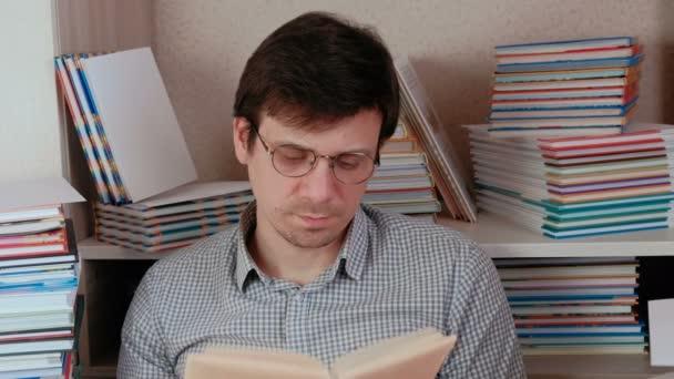 Brunet mladík v brýlích listoval stránkami knihy sedí mezi knihami