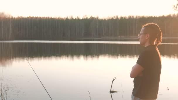 Rybář na rybníku. Mladý kluk s dredy v brýlích v tričko udici ryb.
