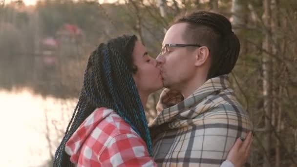 Několik mladých lidí: muž a žena polibek a objetí na břehu řeky při západu slunce. Romantický večer spolu. Dívka s copánky ve vlasech, mladý muž s dredy.