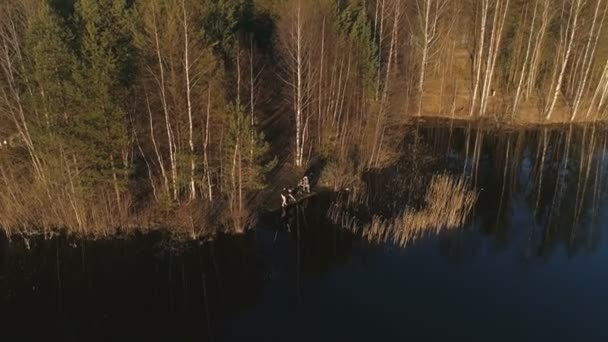 People fishing on the river in the forest. Flying aerial video.