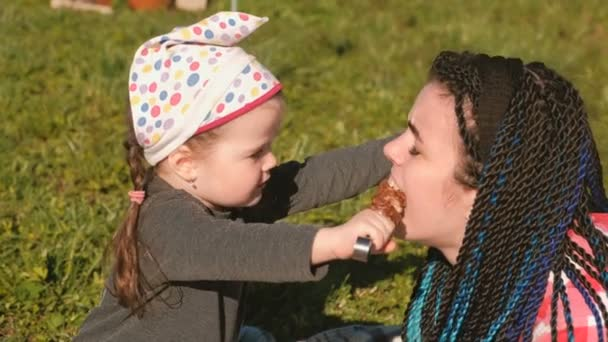 Malá roztomilá dcera krmení její matka s grilování šašlik maso na špízu v zahradě