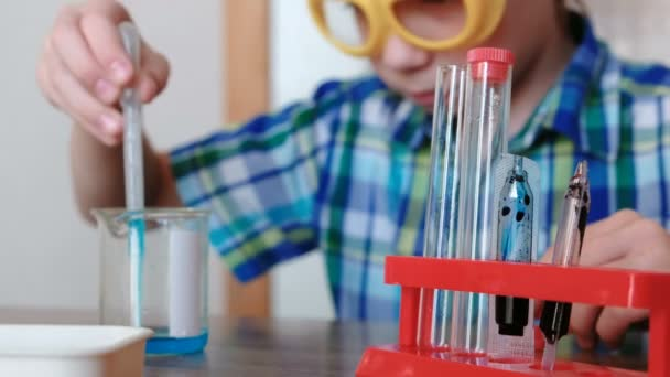 Experiments on chemistry at home. Boy pours blue liquid from the beaker into the test tube with a pipette.