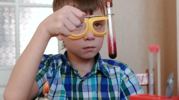 Experiments on chemistry at home. Boy examines the contents of the test tube.