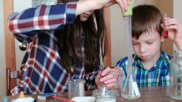 Chemistry experiments at home. Mom pours water from the bottle into the flask using a big pipette.