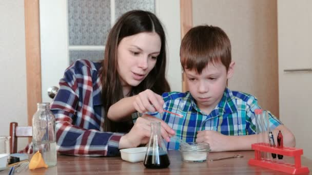 Chemistry experiments at home. Mom and son make a chemical reaction with the release of gas in the flask.