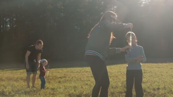 Máma a táta hraje s dětmi, takže mýdlové bubliny na louce v blízkosti lesa, rodinný víkend.
