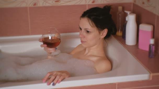 Fiatal gyönyörű barna nő vesz egy fürdőt, iszik a whisky, és mosolyogva