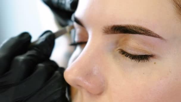 Cosmetologo esegue la procedura del sopracciglio di correzione con le pinzette. Vista del primo piano occhi anteriori