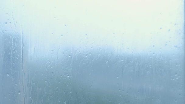 Gocce di pioggia flusso verso il basso il primo piano di vetro