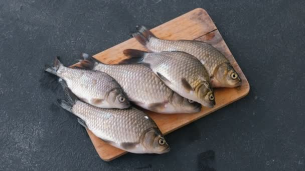 Cooking fish. Fresh small carps on the table on a wooden Board close-up.