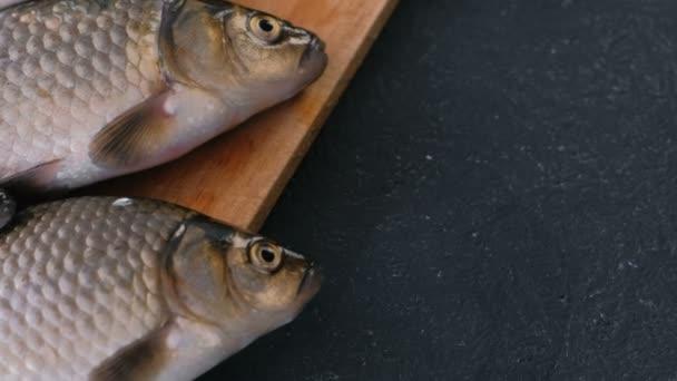 Vaření ryb. Čerstvé malé kapry na stole na dřevěné desce detail.