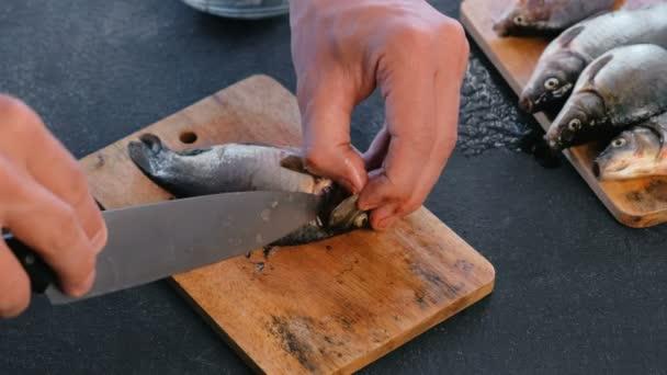 Muž vyjme ploutve kapra ryby na dřevěné desce. Vaření ryb. Rukou zblízka