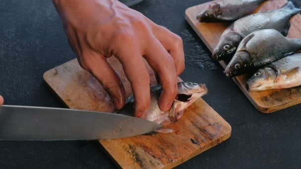 Muž vyjme ploutvemi kapři ryb. Vaření ryb. Rukou zblízka