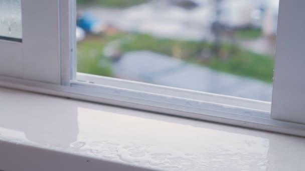 Mokré okenního parapetu s otevřeným oknem v dešti, detail