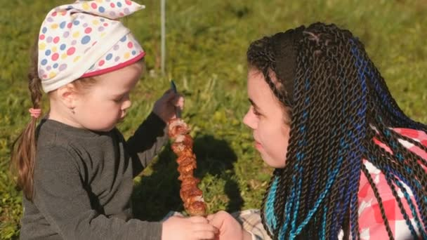Máma krmit její roztomilá malá dcera s grilování šašlik maso na špízu v zahradě