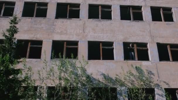 Žena stojící na okně zničených vícepodlažní budovy s mnoha rozbitými okny