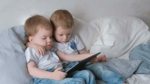 Kids with tablet. Two boys twins toddlers looking cartoon at tablet lying on the bed.
