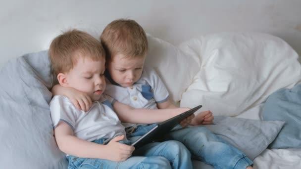 Děti s tabletem. Dva kluky dvojčata batolata hledá karikatury na tablet ležící na posteli.