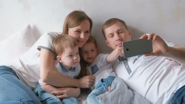Papa macht Familien-Selfie mit Handy. Mama, Papa und zwei Brüder Zwillinge Kleinkinder