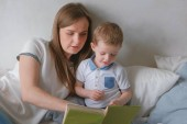 Fotografie Family mom and son toddler read books laying on the bed. Family reading time.