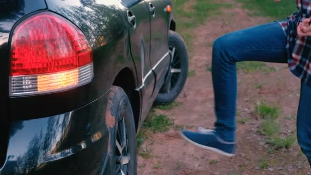 Woman kicks the wheel of the car. Waits for help.