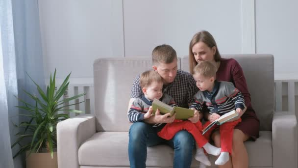 Family mom, dad and two twin brothers read books sitting on the sofa. Family reading time.