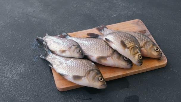 Vaření ryb. Kapři na stole na dřevěné desce detail, boční pohled.