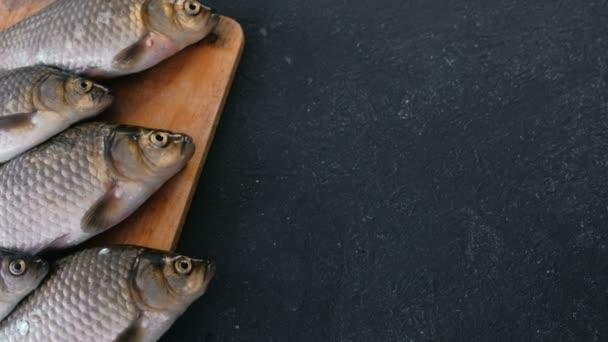 Főzés hal. Az asztalon, fából készült tábla közelről a friss kis ponty.