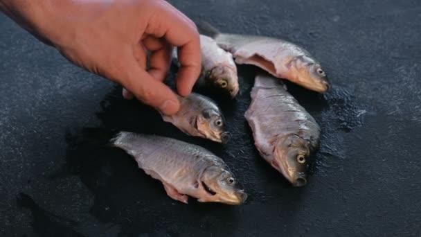 Muž si hraje s kapr čerstvý čisté ryb na černém stole. Vaření ryb. Detail ruční.