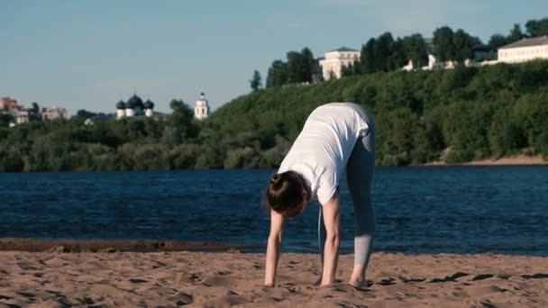 Woman doing yoga on the beach by the river in the city. Beautiful view in Urdhva Mukha shvanasana pose.