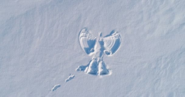 Snow angels print on a snowcovered area. Aerial footage. Camera is close.