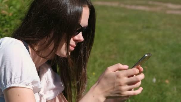 Žena je psaní zprávy na mobilním telefonu sedí v parku v slunečný den. Boční pohled.