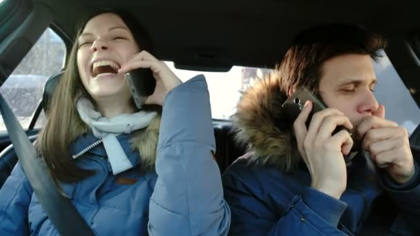 Man and woman speaking their cellphones and hysterical laughing sitting in car.