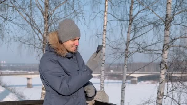 reputable site c893f ab856 Mann in blau Daunenjacke mit Fell Kapuze mit Handy für Video-Chats in  Winter Park.