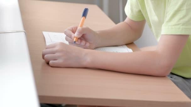 Iskolás gyerek tanul, hogy írjon levelet az asztalnál ülő. Közeli fiúk kezében.
